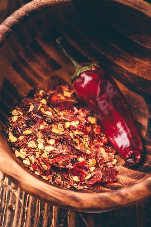 Άλεσε το κόκκινο πιπέρι τσίλι στο ξύλινο κύπελλο στοκ εικόνα
