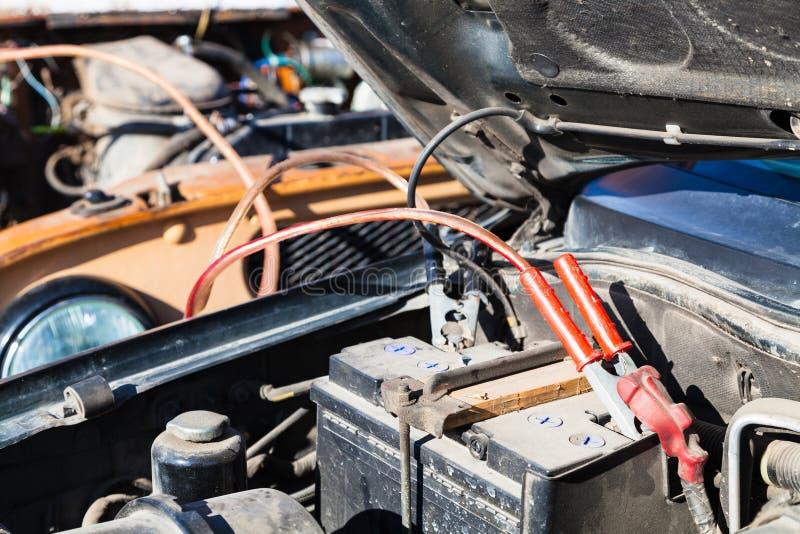 Άλμα που αρχίζει την παλαιά μπαταρία αυτοκινήτων με ένα άλλο όχημα στοκ φωτογραφία