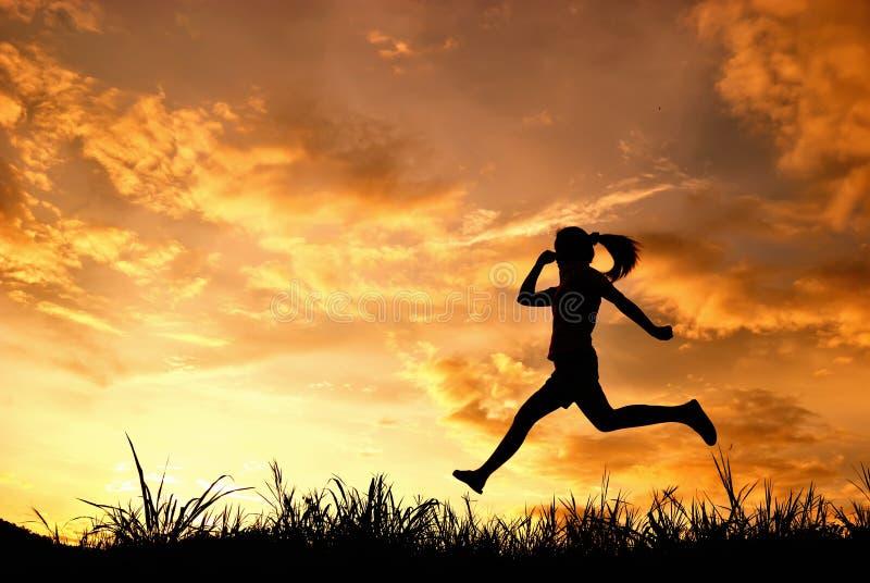 άλμα που τρέχει τη σκιαγραφημένη γυναίκα ηλιοβασιλέματος στοκ φωτογραφίες