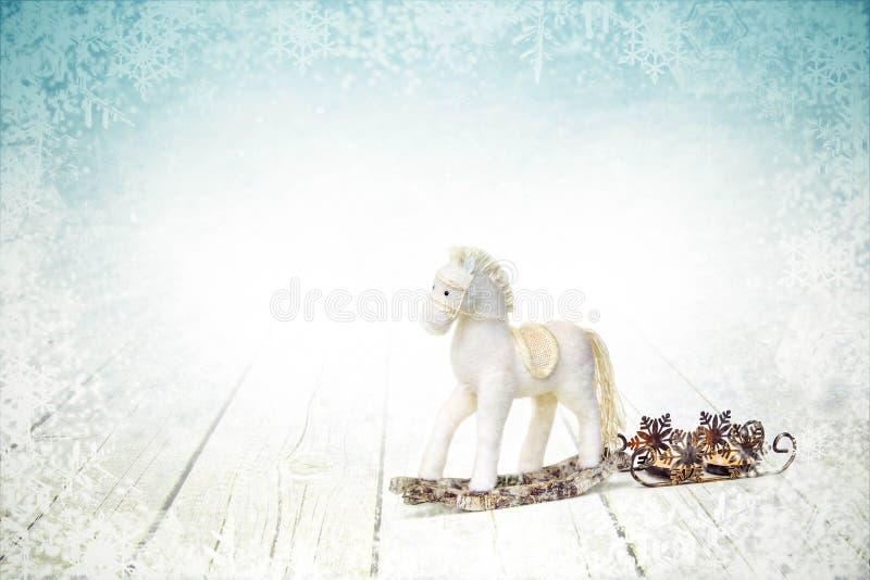 Άλογο και έλκηθρο μπιχλιμπιδιών Χριστουγέννων με τα κεριά στο άσπρο ξύλινο υπόβαθρο στοκ φωτογραφίες