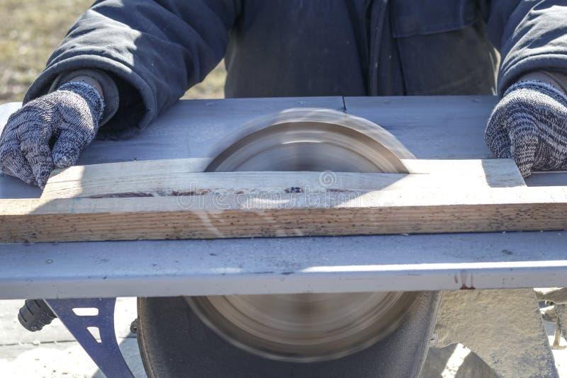 άμεσο λευκό πριονιών λεπίδων ανασκόπησης το αυτοκίνητο πριονίζει το ξύλο υπάρχει ένας πίνακας στο υπόβαθρο Λειτουργώντας χέρι στοκ εικόνα