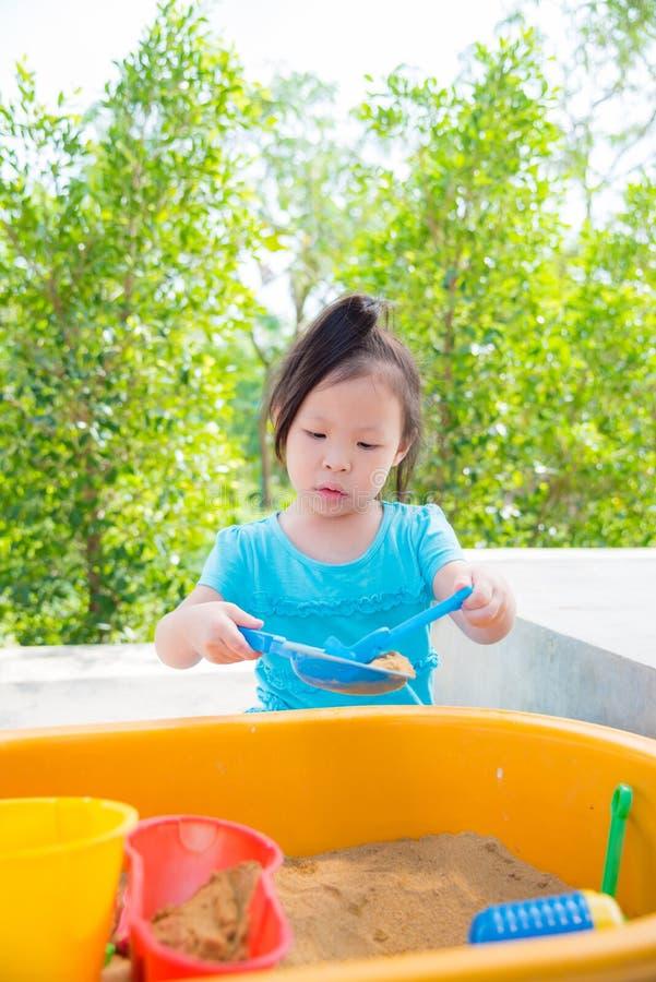 Άμμος παιχνιδιού μικρών κοριτσιών στο Sandbox στοκ εικόνες