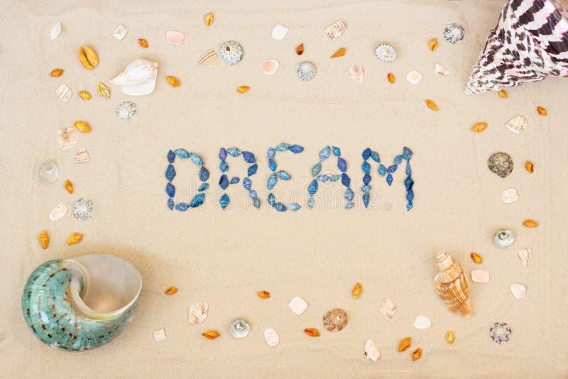 Άμμος στην παραλία το καλοκαίρι, το όνειρο επιγραφής από τα κοχύλια στην άμμο r r στοκ εικόνες