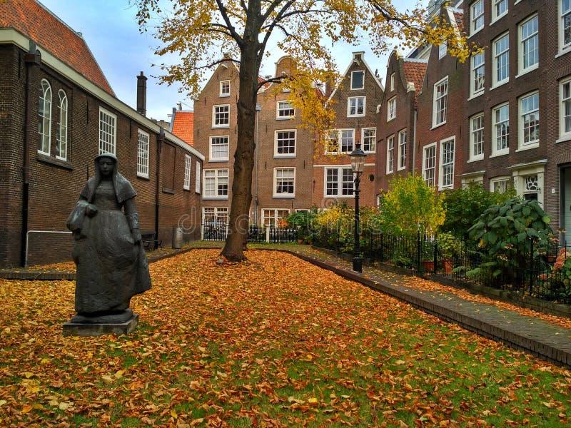 Άμστερνταμ/οι Κάτω Χώρες - 30 Οκτωβρίου 2016: Παλαιό ναυπηγείο Begijnhof με τα σπίτια, τον κήπο και ένα γλυπτό στοκ εικόνα