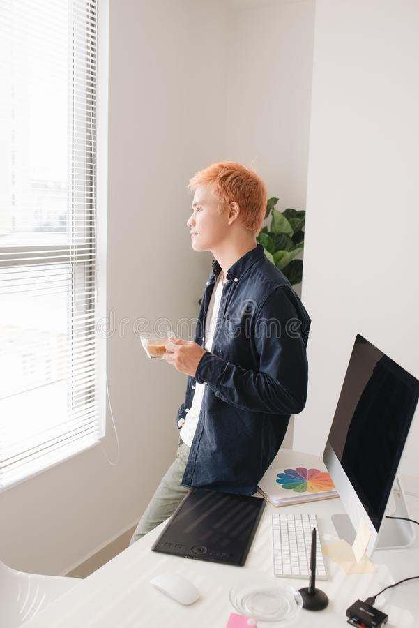 Άνδρας δημιουργικός εργαζόμενος που στέκεται μπροστά από το γραφείο στο δημιουργικό ο στοκ φωτογραφίες με δικαίωμα ελεύθερης χρήσης