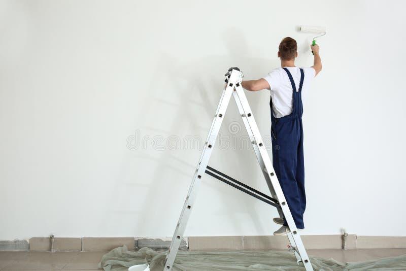 Άνδρας ζωγράφος που χρησιμοποιεί τον κύλινδρο για να ανανεώσει το χρώμα του τοίχου στο εσωτερικό στοκ φωτογραφία