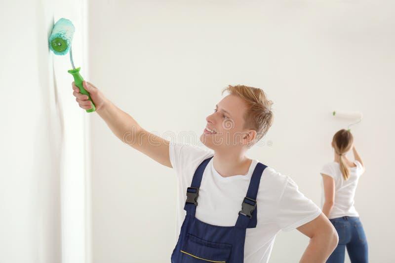 Άνδρας ζωγράφος που χρησιμοποιεί τον κύλινδρο για να ανανεώσει το χρώμα του τοίχου στο εσωτερικό στοκ εικόνα