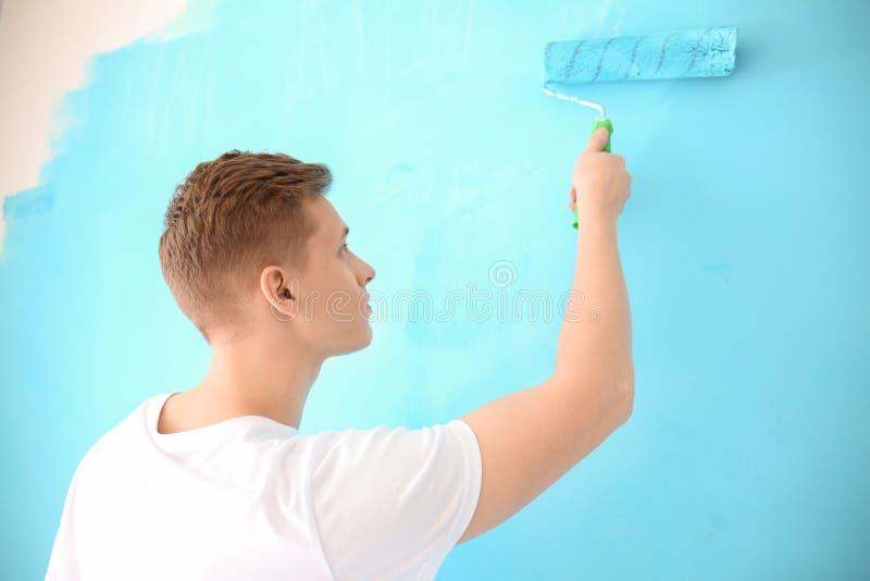 Άνδρας ζωγράφος που χρησιμοποιεί τον κύλινδρο για να ανανεώσει το χρώμα του τοίχου στο εσωτερικό στοκ φωτογραφία με δικαίωμα ελεύθερης χρήσης
