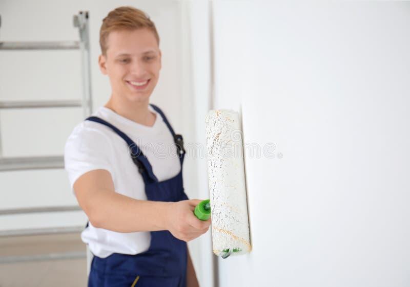 Άνδρας ζωγράφος που χρησιμοποιεί τον κύλινδρο για να ανανεώσει το χρώμα του τοίχου στο εσωτερικό στοκ φωτογραφίες