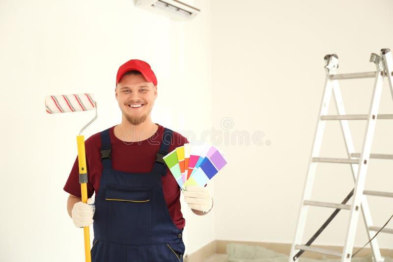 Άνδρας ζωγράφος σε ομοιόμορφο με τα δείγματα παλετών βουρτσών και χρώματος κυλίνδρων στο εσωτερικό στοκ φωτογραφία με δικαίωμα ελεύθερης χρήσης