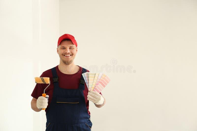 Άνδρας ζωγράφος σε ομοιόμορφο με τα δείγματα παλετών χρώματος και τη βούρτσα κυλίνδρων στο εσωτερικό στοκ εικόνα με δικαίωμα ελεύθερης χρήσης
