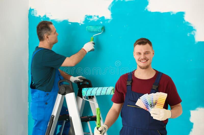 Άνδρας ζωγράφος σε ομοιόμορφο με τα δείγματα παλετών χρώματος και τη βούρτσα κυλίνδρων στο εσωτερικό στοκ φωτογραφίες