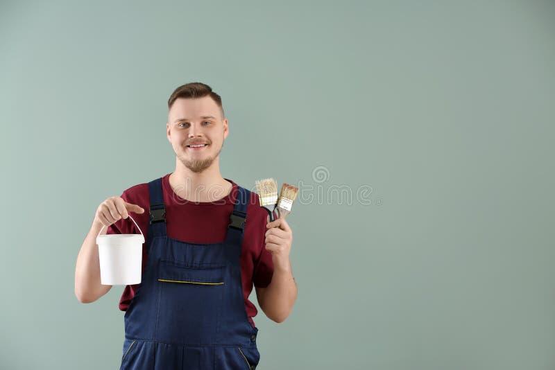 Άνδρας ζωγράφος σε ομοιόμορφο με τις βούρτσες και τον κάδο του χρώματος στο υπόβαθρο χρώματος στοκ εικόνες με δικαίωμα ελεύθερης χρήσης