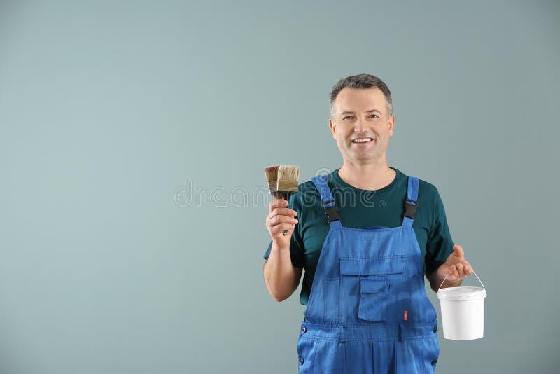 Άνδρας ζωγράφος σε ομοιόμορφο με τις βούρτσες και τον κάδο του χρώματος στο υπόβαθρο χρώματος στοκ φωτογραφία