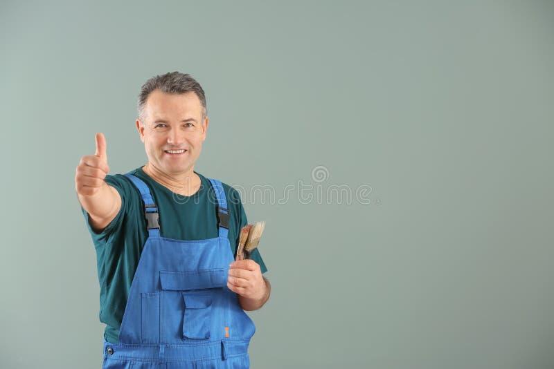 Άνδρας ζωγράφος σε ομοιόμορφο με τις βούρτσες στο υπόβαθρο χρώματος στοκ φωτογραφία με δικαίωμα ελεύθερης χρήσης