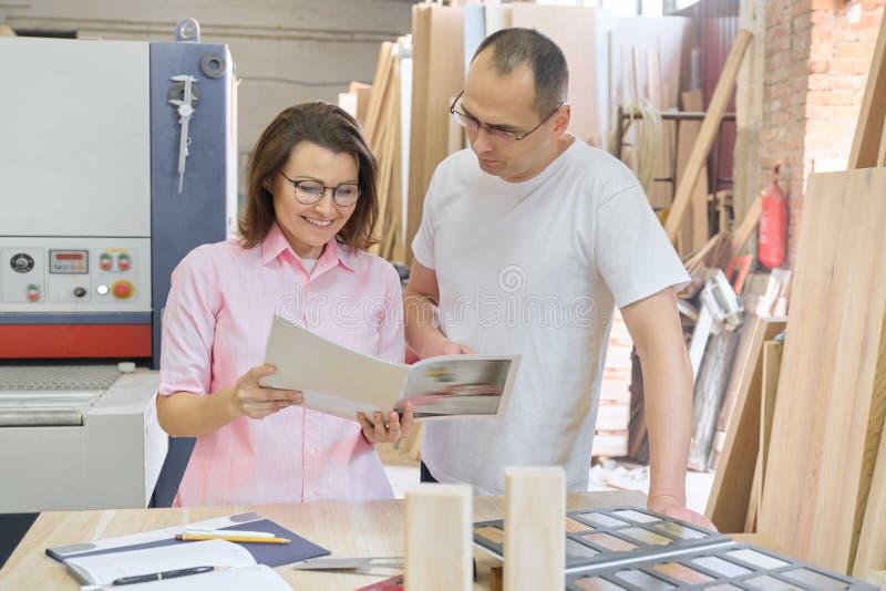 Άνδρας και γυναίκα ζεύγους που επιλέγουν τα ξύλινα προϊόντα, που λειτουργούν τη συζήτηση στοκ φωτογραφία με δικαίωμα ελεύθερης χρήσης