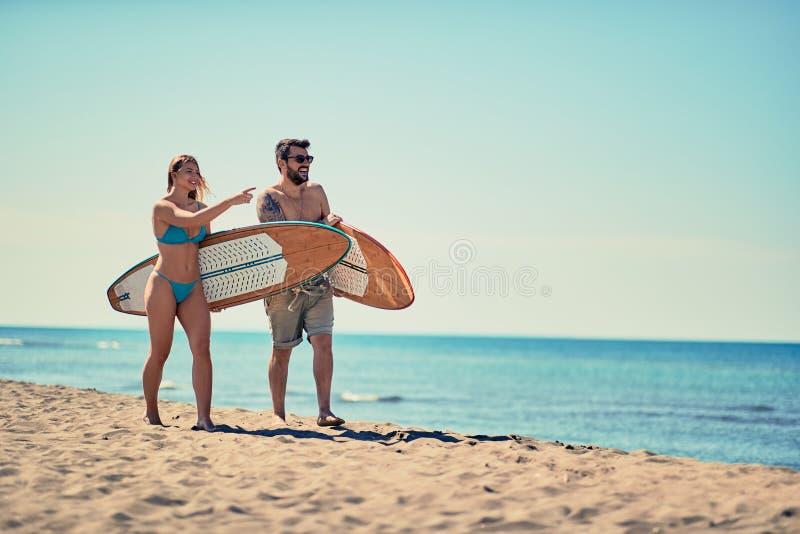 Άνδρας και γυναίκα με έναν πίνακα κυματωγών στις διακοπές παραλιών Το ακραίο s στοκ εικόνα