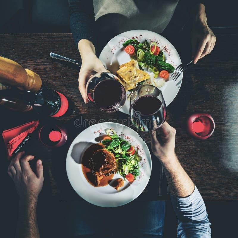Άνδρας και γυναίκα που έχουν το ρομαντικό γεύμα σε ένα εστιατόριο, που τονίζεται imag στοκ φωτογραφία