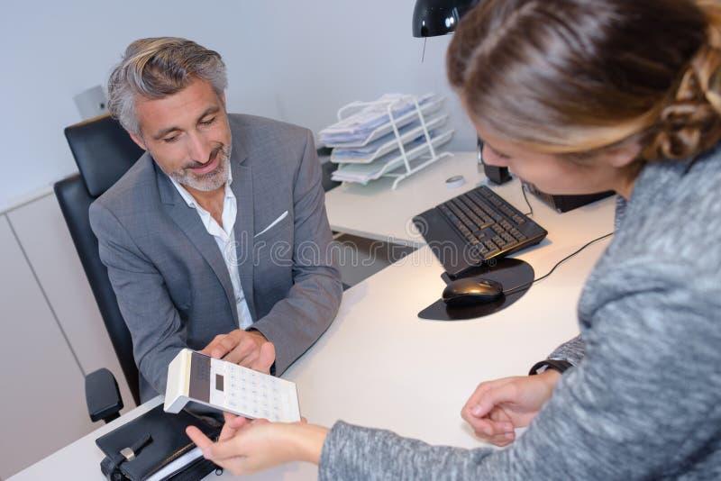 Άνδρας και γυναίκα που εξετάζουν τον υπολογιστή πέρα από το γραφείο στοκ φωτογραφία με δικαίωμα ελεύθερης χρήσης