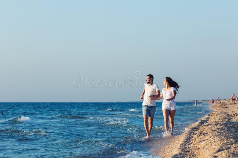 Άνδρας και γυναίκα που οργανώνονται ευτυχώς κατά μήκος της ακτής της θάλασσας στοκ εικόνες