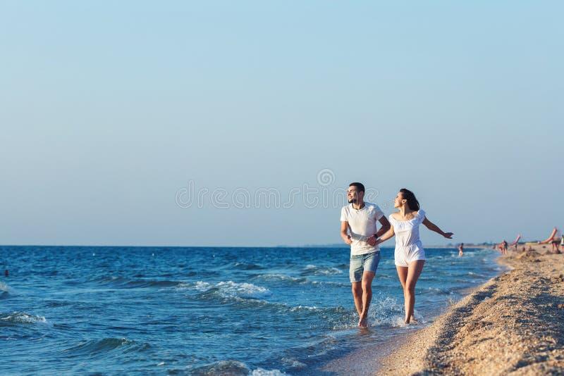 Άνδρας και γυναίκα που οργανώνονται ευτυχώς κατά μήκος της ακτής της θάλασσας στοκ φωτογραφίες