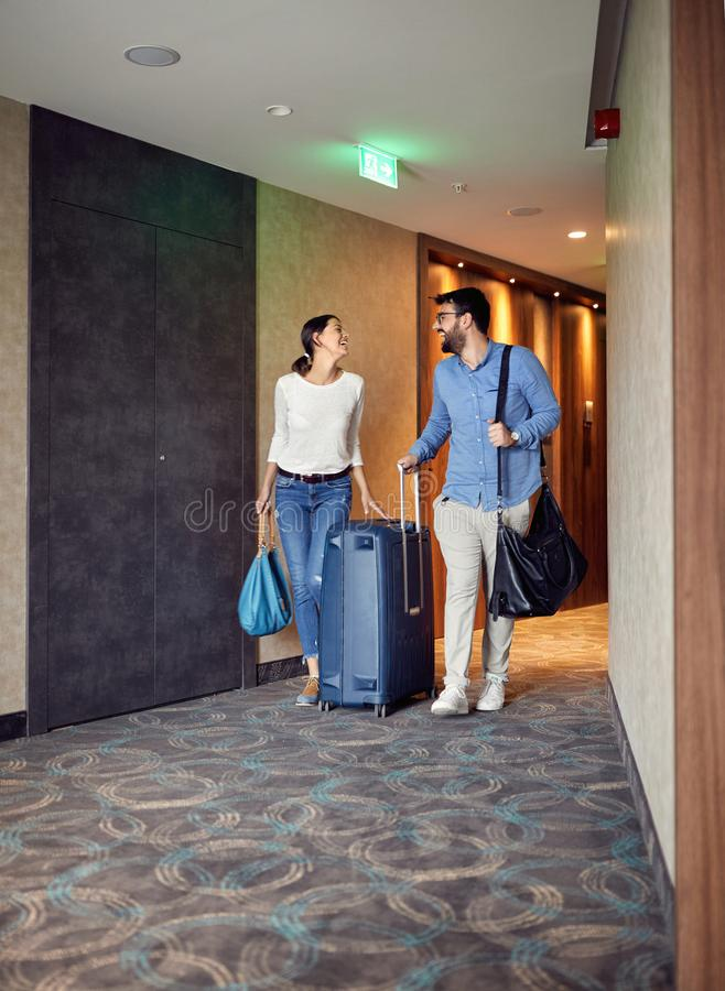 Άνδρας και γυναίκα που φθάνουν στο λόμπι ξενοδοχείων με τη βαλίτσα στοκ εικόνες με δικαίωμα ελεύθερης χρήσης