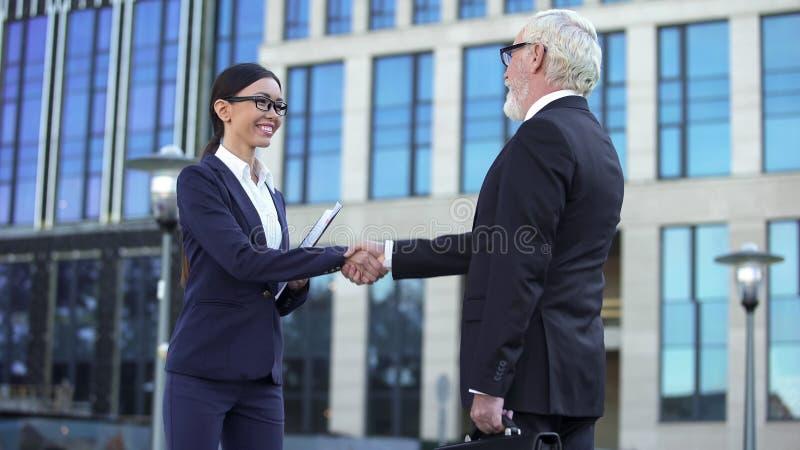 Άνδρας και γυναίκα στα επίσημα ενδύματα που τινάζουν τα χέρια, σημάδι της συνεργασίας, σύμβαση στοκ εικόνα