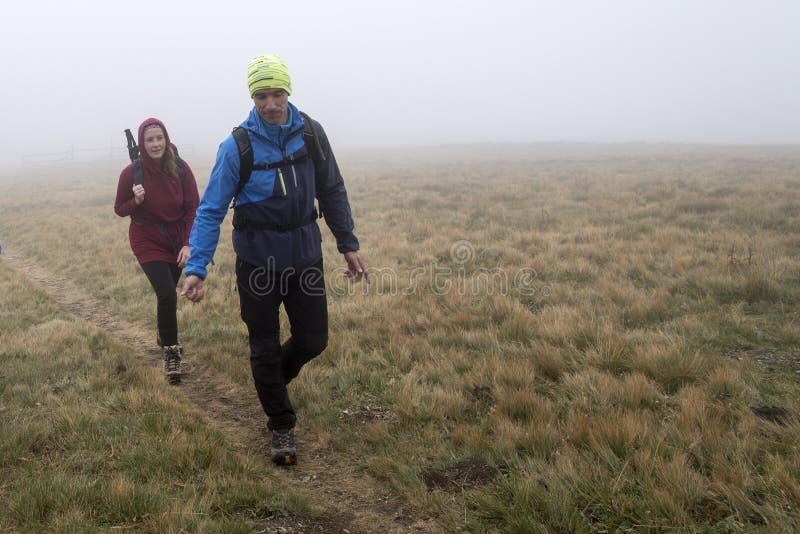 Άνδρας και γυναίκα στο λιβάδι βουνών στην ομίχλη στοκ φωτογραφίες
