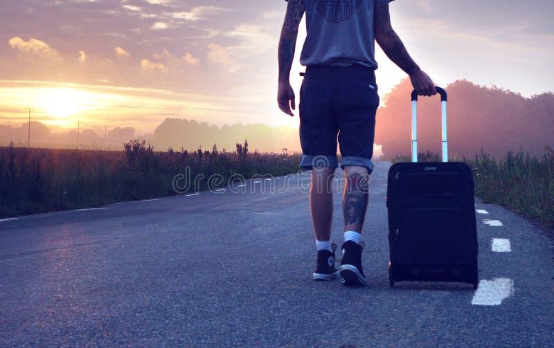 Άνδρας με αποσκευές εν κινήσει κατά τη διάρκεια της δύσης στοκ φωτογραφίες