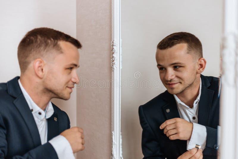 Άνδρας με κοστούμι χαμογελά στην αντανάκλασή του στον καθρέφτη Τέλεια εμφάνιση στοκ εικόνα με δικαίωμα ελεύθερης χρήσης