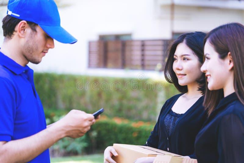 Άνδρας παράδοσης που ζητά από τη γυναίκα για να υπογράψει κινητό για την παράδοση στοκ φωτογραφία με δικαίωμα ελεύθερης χρήσης