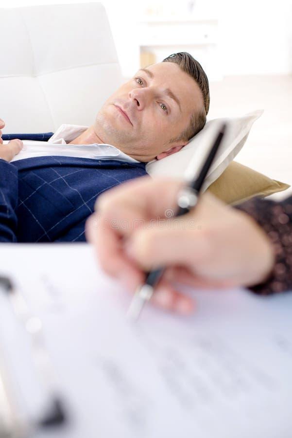 Άνδρας που βάζει στη γυναίκα καναπέδων που παίρνει τις σημειώσεις στοκ εικόνα με δικαίωμα ελεύθερης χρήσης