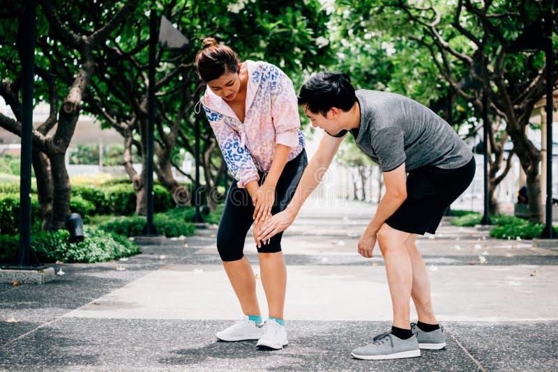 Άνδρας που βοηθά τη γυναίκα με το τραυματισμένο γόνατο στοκ εικόνα με δικαίωμα ελεύθερης χρήσης