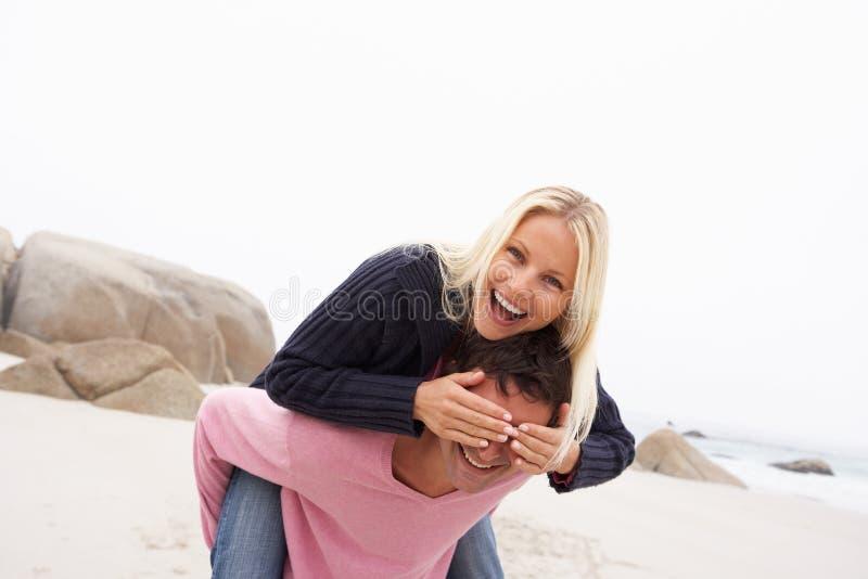 Άνδρας που δίνει το σηκωήταν στην πλάτη γυναικών στη χειμερινή παραλία στοκ εικόνα