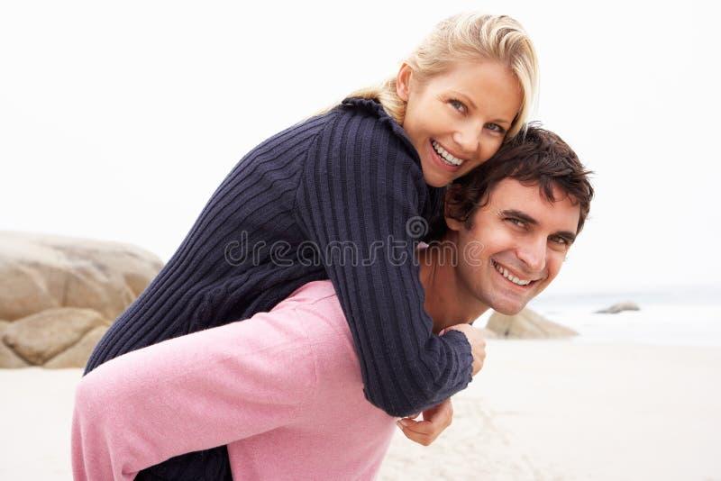 Άνδρας που δίνει το σηκωήταν στην πλάτη γυναικών στη χειμερινή παραλία στοκ φωτογραφίες με δικαίωμα ελεύθερης χρήσης