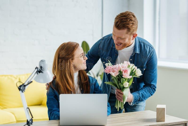 Άνδρας που εκπλήσσει τη νέα εργασία γυναικών από το lap-top με μια ανθοδέσμη στοκ εικόνες με δικαίωμα ελεύθερης χρήσης