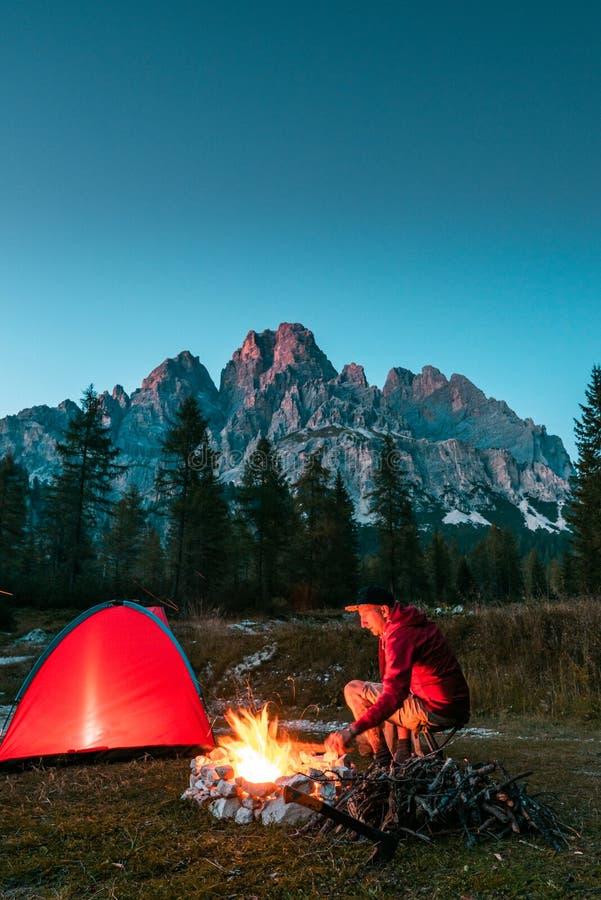 Άνδρας που κάθεται δίπλα στο Campfire και την Άγρια Κατασκήνωση στα Βουνά Ιδέα περιπέτειας στοκ φωτογραφίες