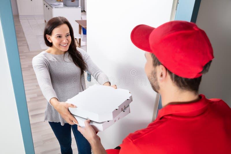 Άνδρας που παραδίδει την πίτσα στη γυναίκα στοκ φωτογραφία με δικαίωμα ελεύθερης χρήσης