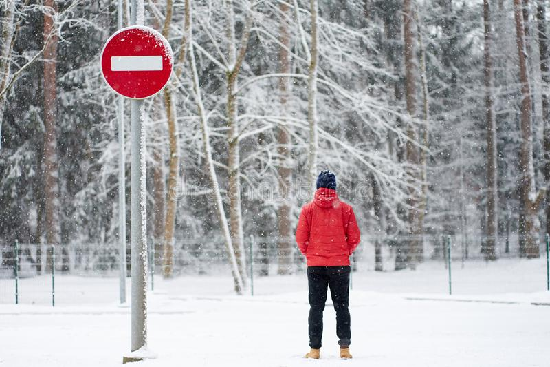 Άνδρας που φοράει κόκκινο χειμερινό μπουφάν και στέκεται κοντά σε καμία οδική πινακίδα κατά τη διάρκεια της χιονόπτωσης στοκ εικόνες