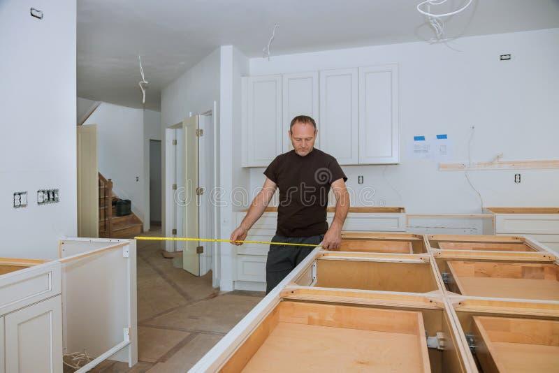 0Άνδρας που χρησιμοποιεί μαγνητοταινία για μετρήσεις στην κουζίνα για βελτίωση του σπιτιού στοκ φωτογραφία