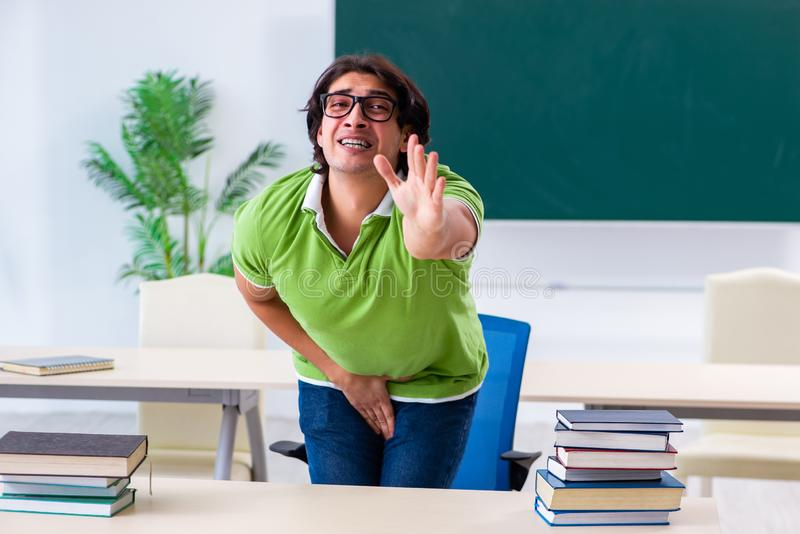 Άνδρας σπουδαστής που πάσχει από την ώθηση στην τάξη στοκ εικόνα