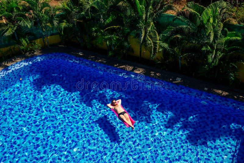 Άνδρας χαλαρώνει στο φουσκωτό ροζ στρώμα του κρεβατιού στις διακοπές της πισίνας στοκ φωτογραφίες