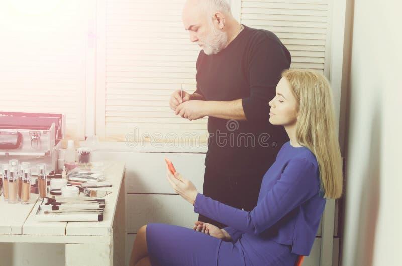 Άνδρας Visagiste που προετοιμάζει τη βούρτσα για το πρόσωπο γυναικών makeup στοκ φωτογραφία με δικαίωμα ελεύθερης χρήσης