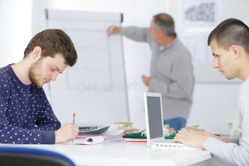 Άνδρες σπουδαστές που εργάζονται στην τάξη στοκ εικόνες