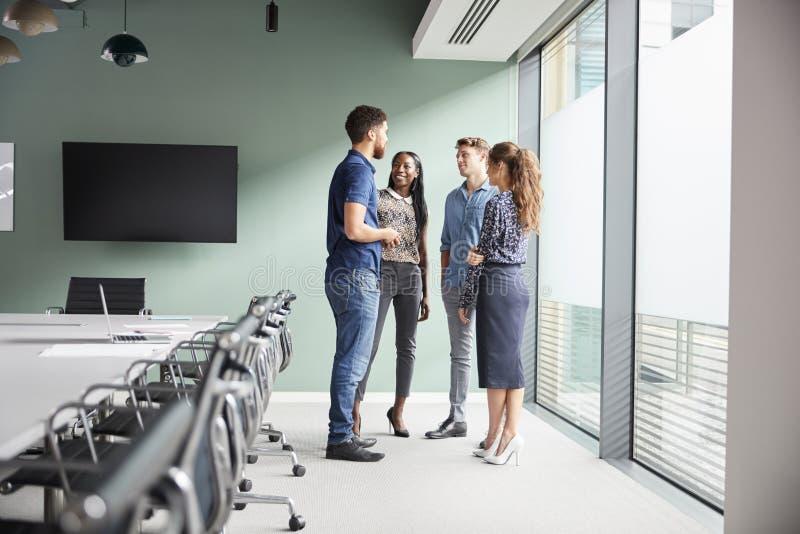 Άνετα ντυμένοι επιχειρηματίες και επιχειρηματίες που διοργανώνουν την άτυπη συνεδρίαση στη σύγχρονη αίθουσα συνεδριάσεων στοκ εικόνα