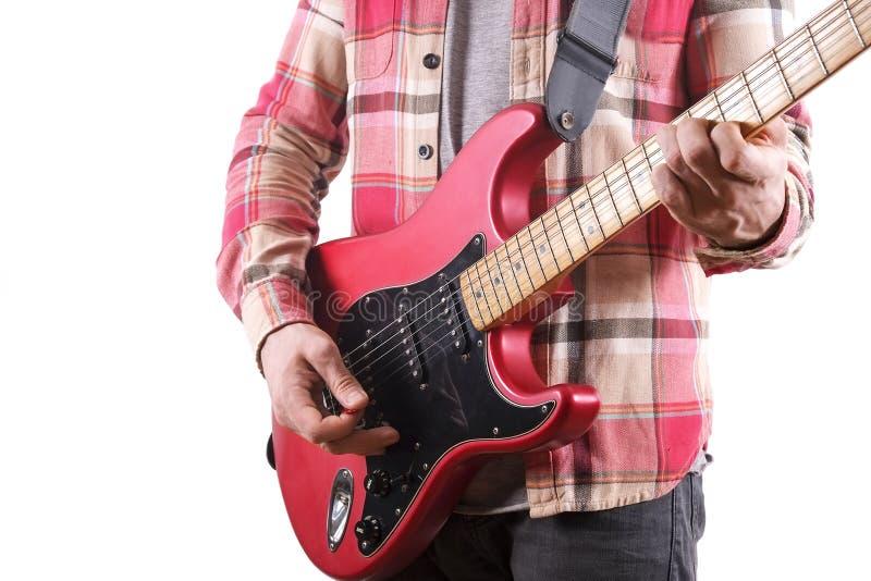 Άνετα ντυμένος νεαρός άνδρας με τα παίζοντας τραγούδια κιθάρων που απομονώνονται στο λευκό πίνακας lap-top Σε απευθείας σύνδεση έ στοκ φωτογραφία