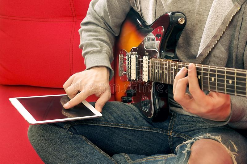 Άνετα ντυμένος νεαρός άνδρας με τα παίζοντας τραγούδια κιθάρων στο δωμάτιο στο σπίτι Σε απευθείας σύνδεση έννοια μαθημάτων κιθάρω στοκ φωτογραφίες με δικαίωμα ελεύθερης χρήσης