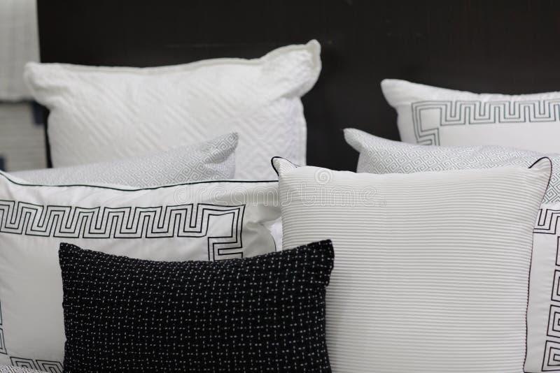 Άνετα χνουδωτά μαξιλάρια σε μια ταξινομημένη βασιλιάς κρεβατοκάμαρα κρεβατιών στοκ φωτογραφία