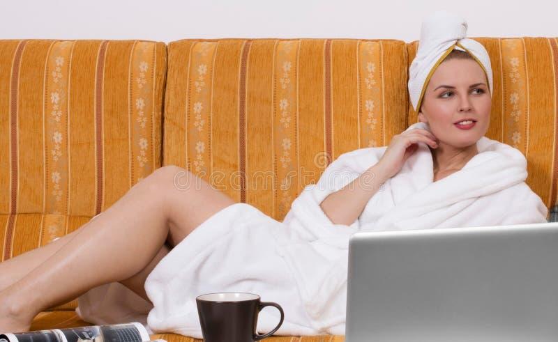 Άνετη γυναίκα στο μπουρνούζι στον καναπέ στοκ εικόνα με δικαίωμα ελεύθερης χρήσης