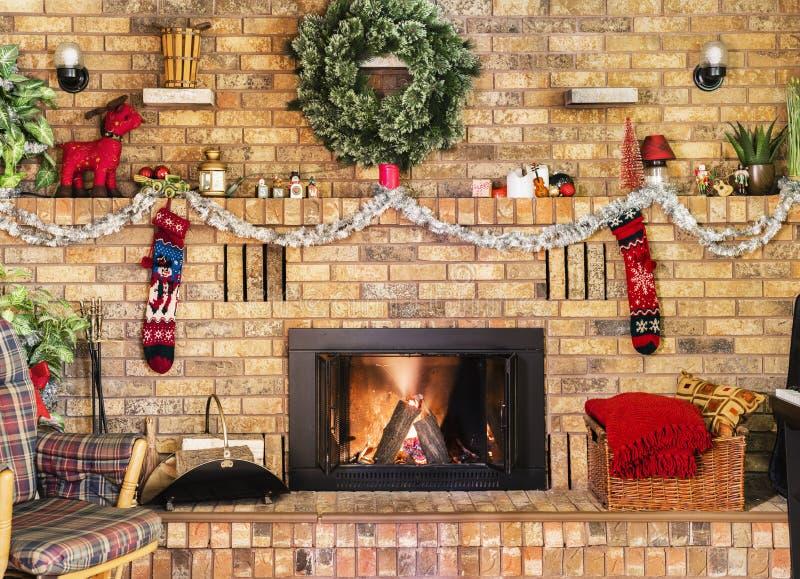 Άνετη πυρκαγιά στην εστία τούβλου και μανδύας που διακοσμείται για τα Χριστούγεννα στοκ εικόνες